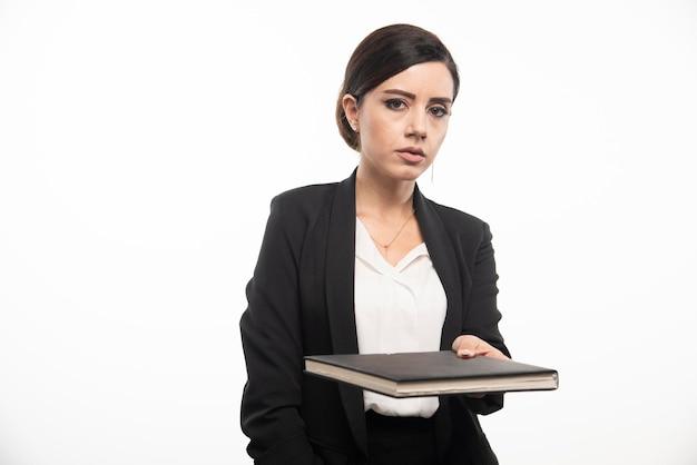 Jeune employé donnant un cahier sur fond blanc. photo de haute qualité
