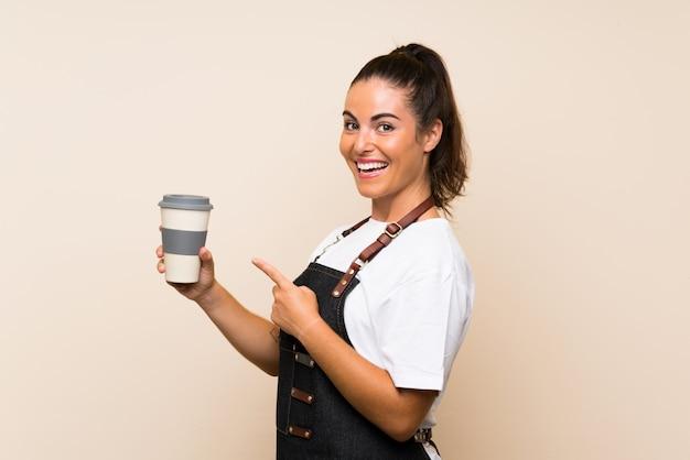 Jeune employé femme tenant un café à emporter et en le pointant