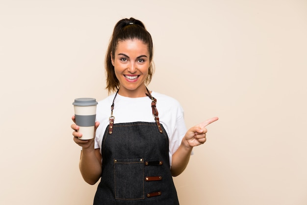 Jeune employé femme tenant un café à emporter surpris et un doigt pointé sur le côté