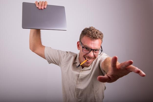 Un jeune employé fou avec un ordinateur portable à la main et un stylo dans la bouche, il porte des lunettes