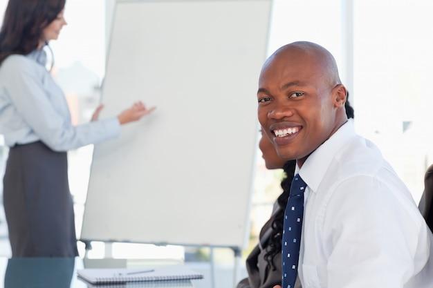Jeune employé portant une chemise blanche tout en étant assis à un bureau dans une salle de réunion