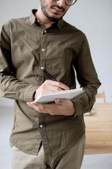 Jeune employé sérieux de sexe masculin dans des vêtements décontractés, prendre des notes dans un ordinateur portable tout en organisant le travail au bureau