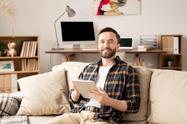 Jeune employé souriant avec tablette assis sur un canapé à la maison