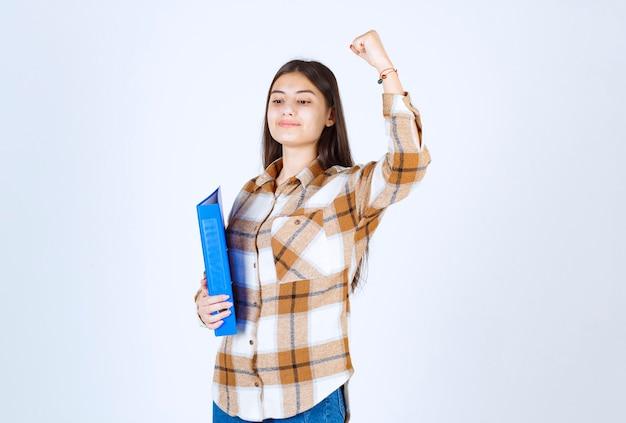 Jeune employé tenant un dossier bleu sur un mur blanc.