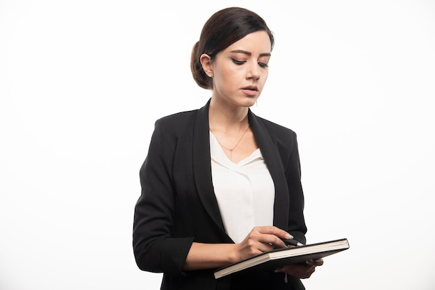 Jeune employé vérifiant le cahier sur fond blanc. photo de haute qualité