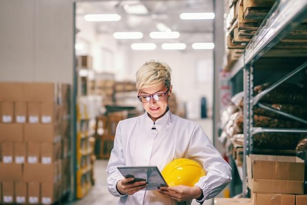 Jeune employée blonde de race blanche avec un casque de protection sous les aisselles à l'aide d'une tablette en se tenant debout dans l'entrepôt.