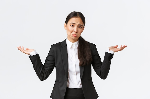 Une jeune employée de bureau asiatique bouleversée, une directrice en costume noir, haussant les épaules avec les mains écartées sur le côté et faisant la moue inconsciente, ne sait pas, ne peut pas comprendre, debout inutile et indécise