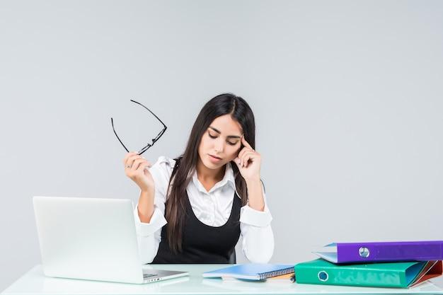 Jeune employée de bureau fatiguée, fatiguée et épuisée en costume gris sur blanc