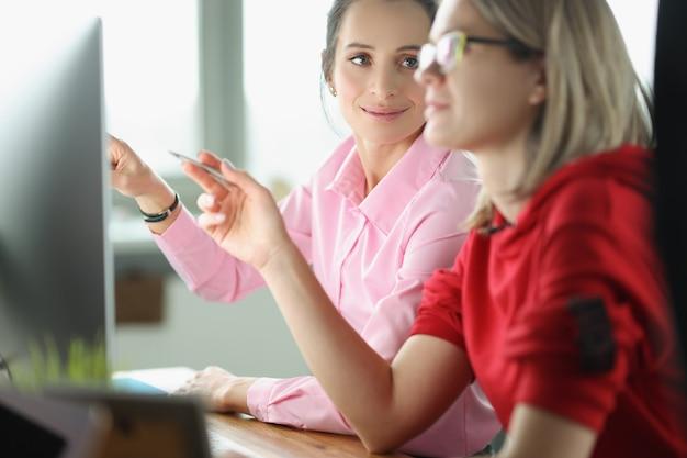 Une jeune employée expérimentée portant des lunettes explique à un collègue l'analyse commerciale