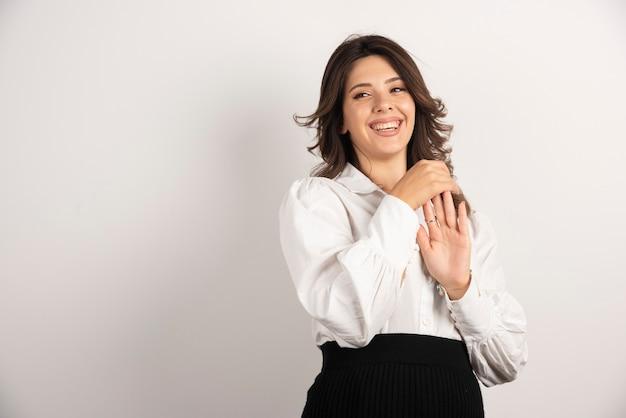 Jeune employée montrant sa main en souriant.