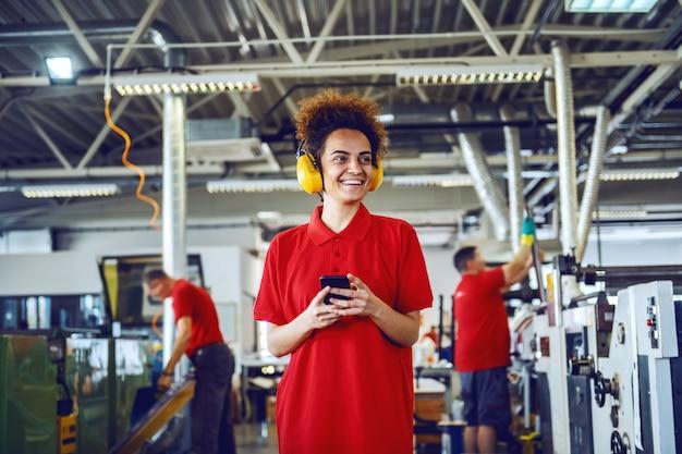 Jeune employée de race blanche gaie aux cheveux bouclés debout dans l'imprimerie et à l'aide de téléphone intelligent pour envoyer des sms.