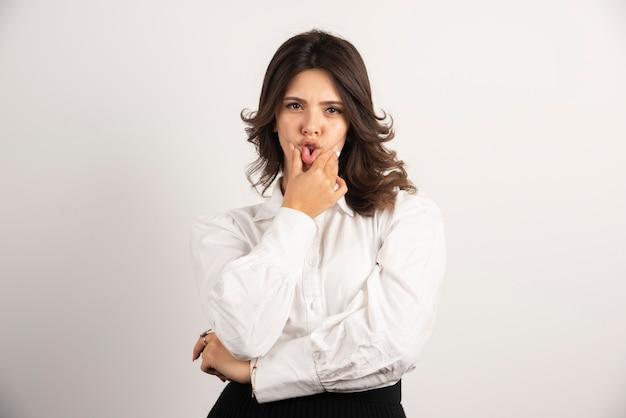 Jeune employée tenant sa bouche sur blanc.