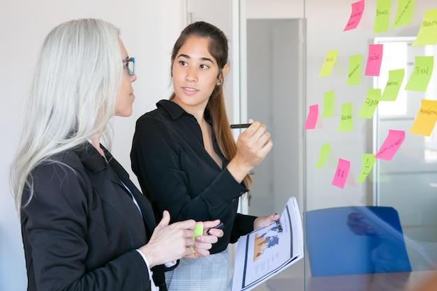 Jeune employeur latin tenant un stylo et des documents statistiques et regardant le patron. collègue de formation de gestionnaire aux cheveux gris confiant et concentré