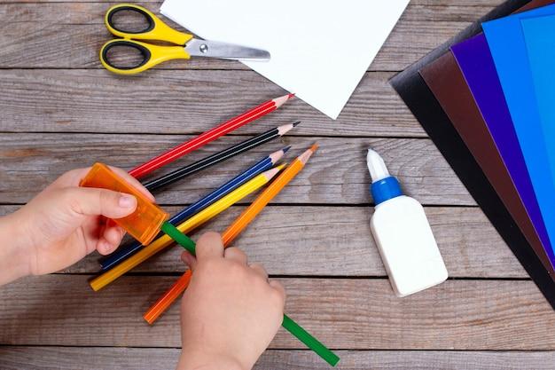 Jeune enfant aiguise des crayons sur fond de bois