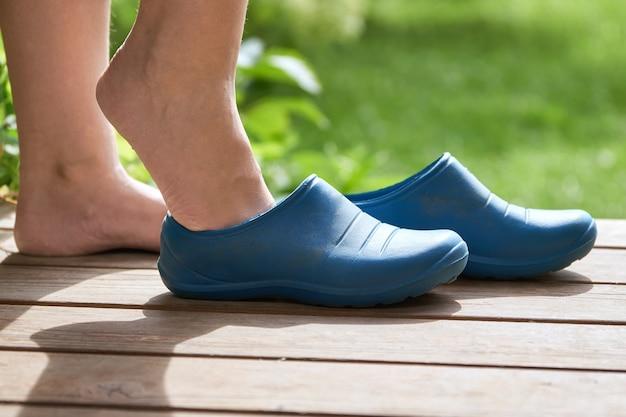 Jeune enfant aux pieds nus avec des bottes en caoutchouc