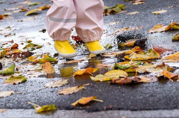 Un jeune enfant avec des bottes jaunes éclabousse dans une flaque de pluie avec des feuilles d'automne