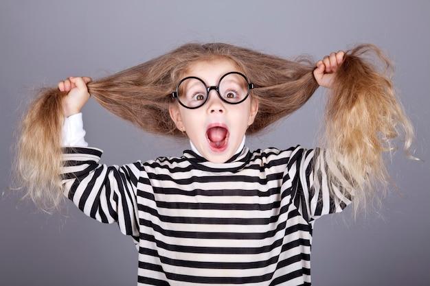 Jeune enfant criant dans des lunettes et une veste tricotée à rayures.