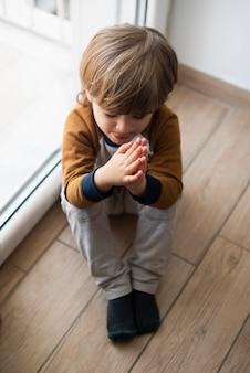 Jeune enfant disant une prière à la maison