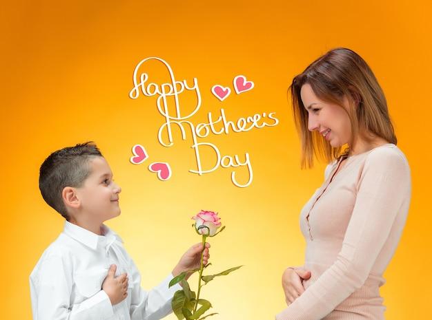 Jeune enfant donnant une rose rouge à sa mère. concept de bonne fête des mères