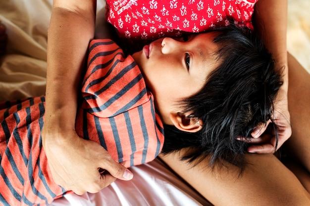 Jeune enfant dormant sur les genoux de sa mère