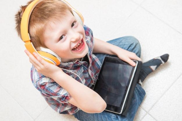 Jeune enfant écoute de la musique avec un casque sur tablette