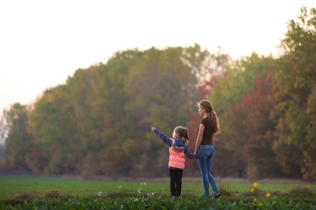 Jeune enfant fille pointe au loin en tenant la main de sa mère