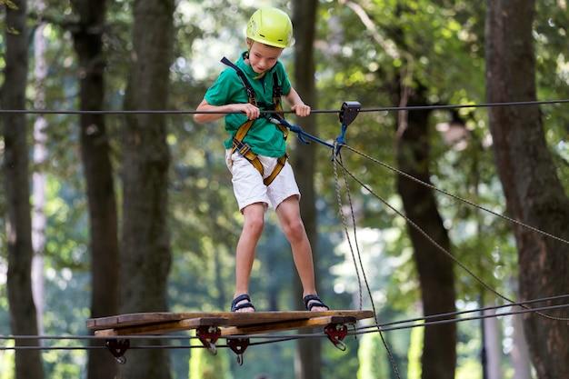Jeune enfant garçon dans le harnais de sécurité et casque attaché avec une carabine à câble sur le chemin de la corde dans le parc.