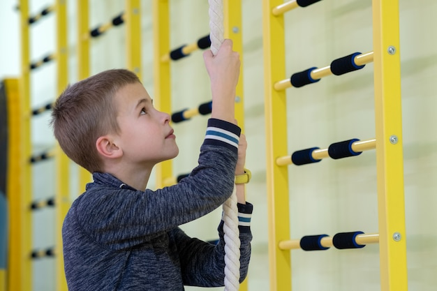 Jeune enfant garçon exerçant sur une barre d'échelle murale à l'intérieur de la salle de gym sportive dans une école.