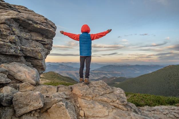 Jeune enfant garçon randonneur debout avec les mains levées dans les montagnes, profitant d'une vue sur le magnifique paysage de montagne au coucher du soleil.