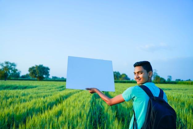 Jeune enfant indien avec affiche vierge au champ de blé indien