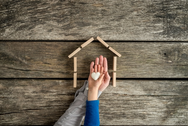 Jeune enfant et son père indiquant leur amour pour une maison dans une image conceptuelle avec leurs mains tenant un cœur à l'intérieur du cadre d'une maison.
