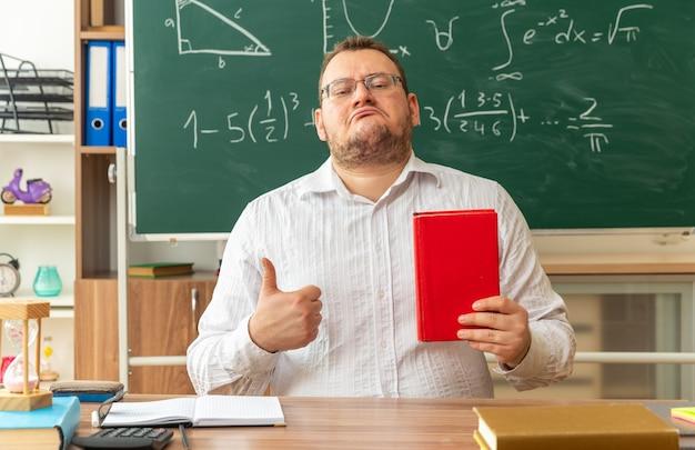 Jeune enseignant confiant portant des lunettes assis au bureau avec des fournitures scolaires en classe tenant un livre fermé montrant le pouce vers l'avant
