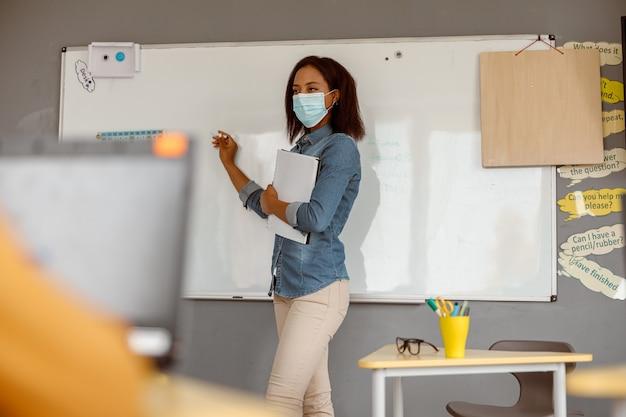 Jeune enseignant dans un masque debout dans la salle de classe