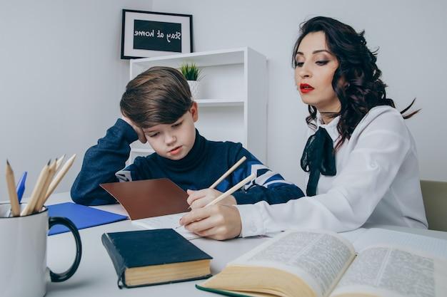 Jeune enseignant essayant d'expliquer des informations au garçon. éduquer ensemble.