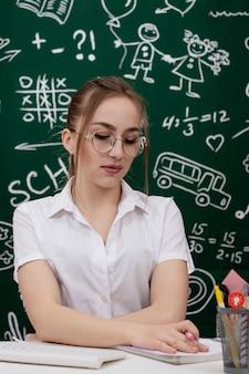 Jeune enseignant est assis près du tableau noir en classe.