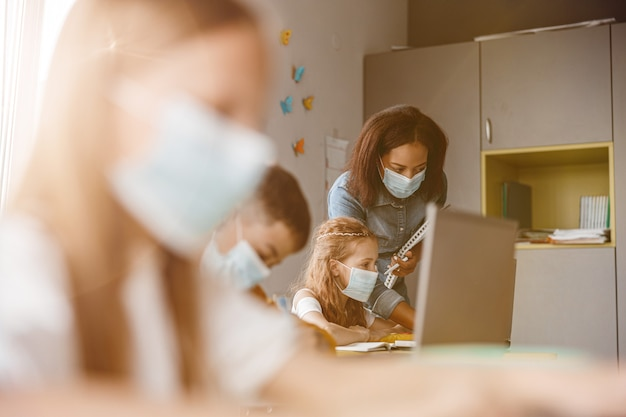 Jeune enseignant et fille regardant un écran d'ordinateur portable en classe