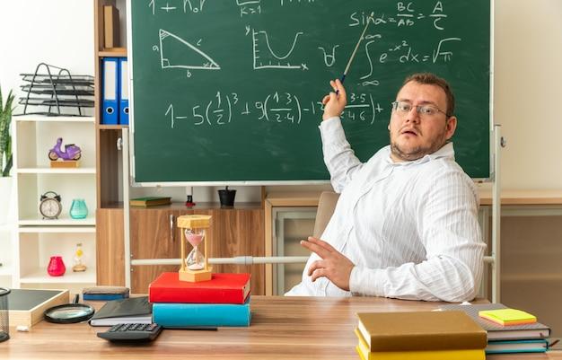 Jeune enseignant impressionné portant des lunettes assis au bureau avec des fournitures scolaires en classe regardant l'avant pointant sur un tableau avec un bâton de pointeur
