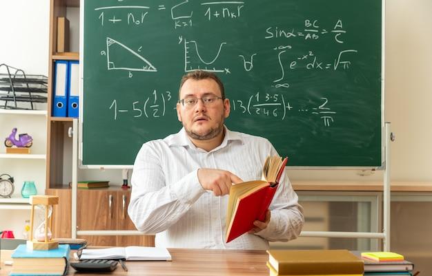 Jeune enseignant impressionné portant des lunettes assis au bureau avec des fournitures scolaires en classe tenant un livre ouvert pointant vers lui regardant à l'avant