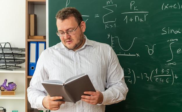 Jeune enseignant impressionné portant des lunettes debout devant le tableau dans le bloc-notes de lecture en classe
