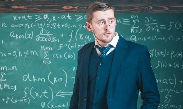 Jeune enseignant à lunettes posant en classe. concept d'éducation d'élite.