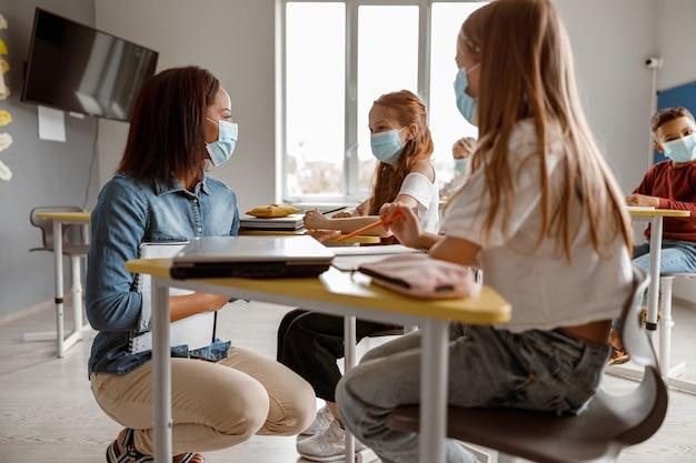Jeune enseignant parlant à deux écolières en classe