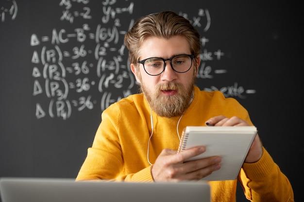 Jeune enseignant pensif barbu à lunettes à l'écoute de l'un des élèves tout en regardant l'écran de l'ordinateur portable pendant la leçon en ligne d'algèbre
