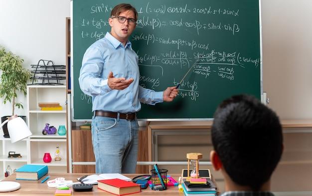 Jeune enseignant portant des lunettes ayant l'air confus et mécontent d'expliquer la leçon aux élèves, debout près du tableau noir avec des formules mathématiques en classe