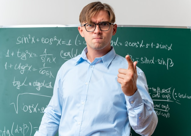 Jeune enseignant portant des lunettes à mécontent et en colère debout près du tableau noir avec des formules mathématiques en classe