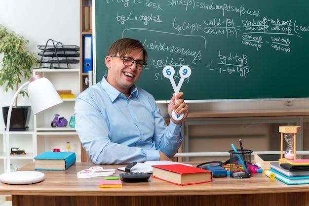 Jeune enseignant portant des lunettes montrant des plaques d'immatriculation expliquant la leçon souriant assis au bureau de l'école avec des livres et des notes devant le tableau noir en classe
