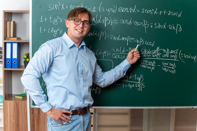Jeune enseignant portant des lunettes tenant une craie expliquant la leçon debout près du tableau noir avec des formules mathématiques en classe