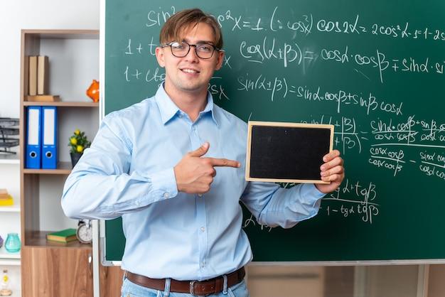 Jeune enseignant portant des lunettes tenant un petit tableau noir pointant avec l'index sur lui souriant confiant debout près du tableau noir avec des formules mathématiques en classe
