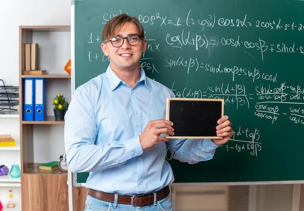 Jeune enseignant portant des lunettes tenant un petit tableau noir à la recherche d'un sourire confiant debout près du tableau noir avec des formules mathématiques en classe