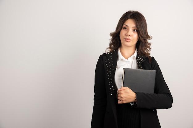 Jeune enseignant posant avec livre sur blanc.