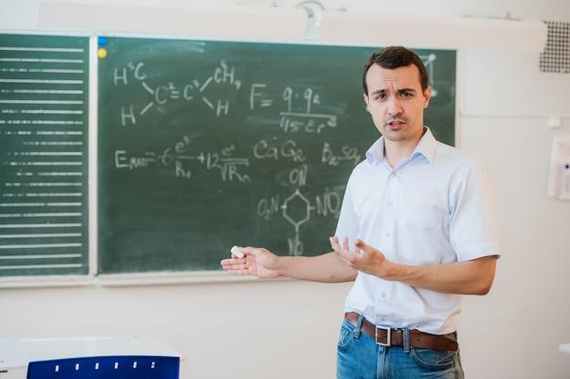 Jeune enseignant près de tableau noir en classe d'école parler à la classe